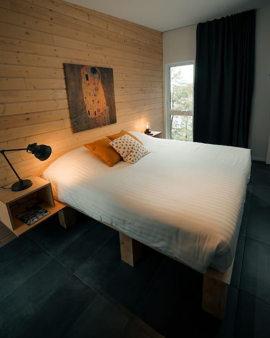 Chambre des maitres avec très grand lit et grande fenestration avec vue sur le lac