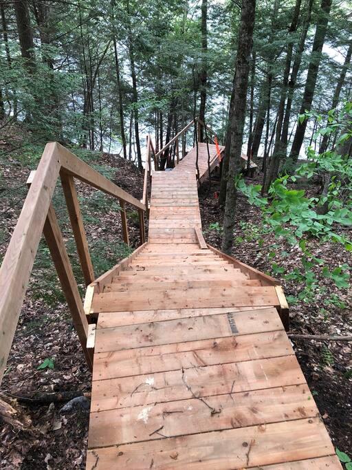 Un sentier avec des escaliers sépare les mini chalets du lac.